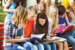 Groupe d'étudiants assis sur un banc en extérieur en train de réviser