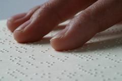 Plan serré sur doigts lisant texte en braille
