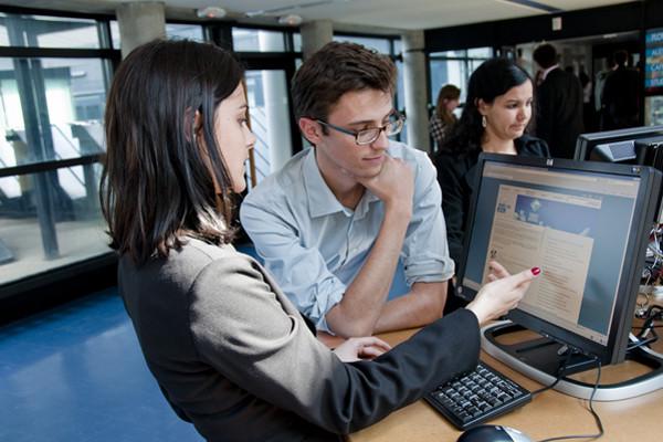 Étudiants devant des postes d'ordinateurs